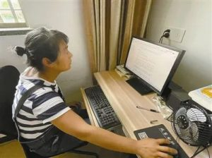 side view of woman sitting at home and working on a computer