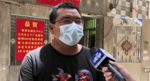 man in mask giving interview in china