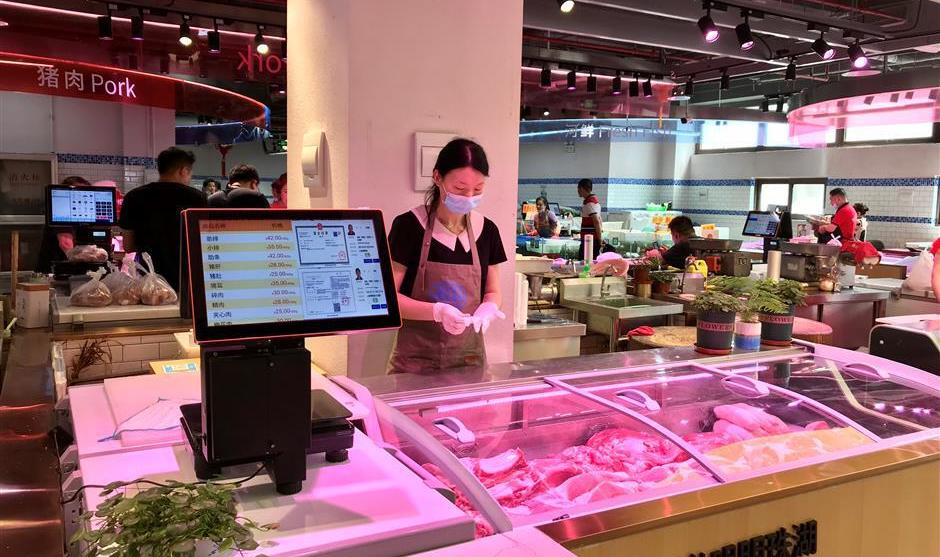 women selling meat with electronic scales and till at wet market in china