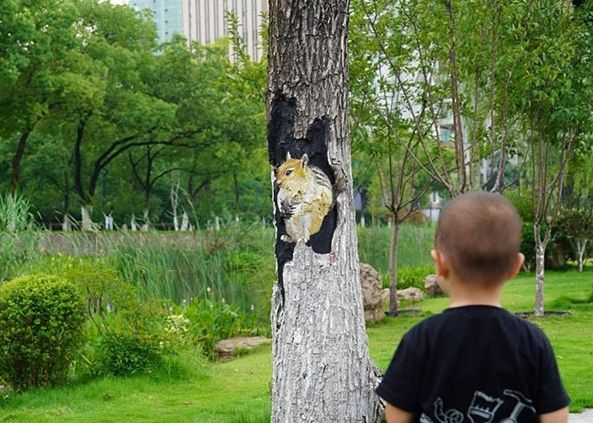 boy looking at squirrel painted on tree in wuhan, china