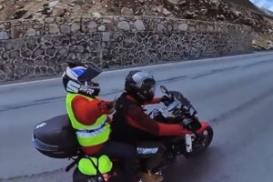 side view of son and mother travelling on mountain road by motorcycle in china
