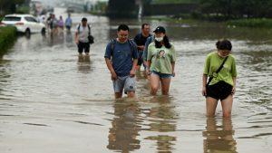 people wading through water after floods in zhengzhou, china