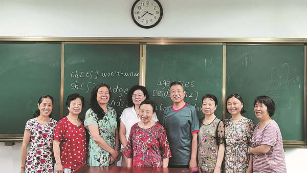 elderly woman posing for picture with university classmates