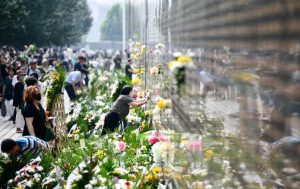 people laying flowers at tangshan earthquake memorial wall