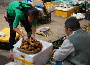 vendor sorting mushrooms at street market in china