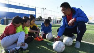 school principle and sports coach with students on football pitch