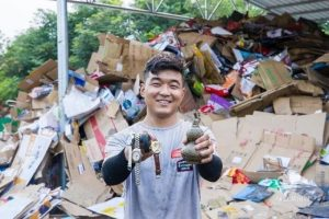 young man showing items found in rubbish heap in china