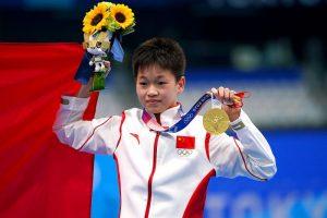 teen diver quan hongchan on podium with gold medal at tokyo olympics