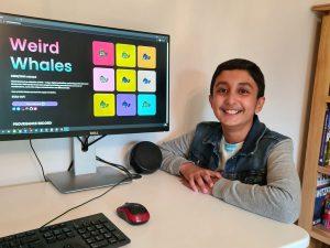 Benyamin Ahmed sitting next to computer showing whale designs