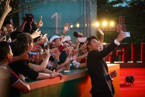 celebrity taking selfie with fans on red carpet in china