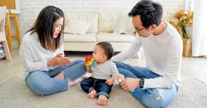asian parents with baby at home in living room