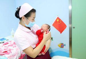 nurse holding newborn baby and china flag