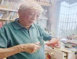 elderly man making butterfly paper cutouts in china