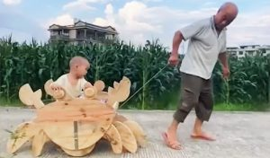 grandfather pulling grandson in home-made wooden crab cart in china