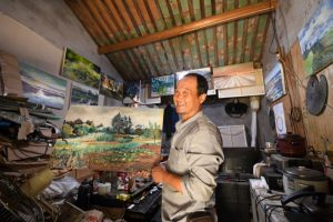 man holding painting in home art studio in china