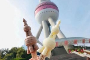 shanghai oriental pearl tower ice creams held up un front of the actual building in shanghai