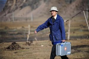 elderly doctor in blue coat carrying case outside in china
