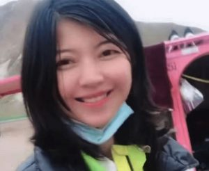 chinese livestream traveller meimei posing for picture in front of vehicle