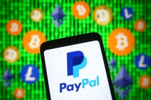 paypal on mobile phone in front of cryptocurrency symbols