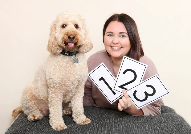 dog owner with dog and number cards