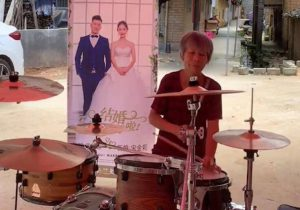 grandma playing on drums at wedding in china