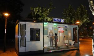 woman holding mobile phone standing outside smart toilet in shanghai
