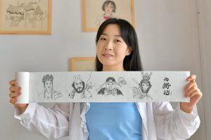 woman showing pictures drawn on tissue paper in china