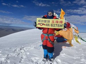 young boy holding sign on mountain climb